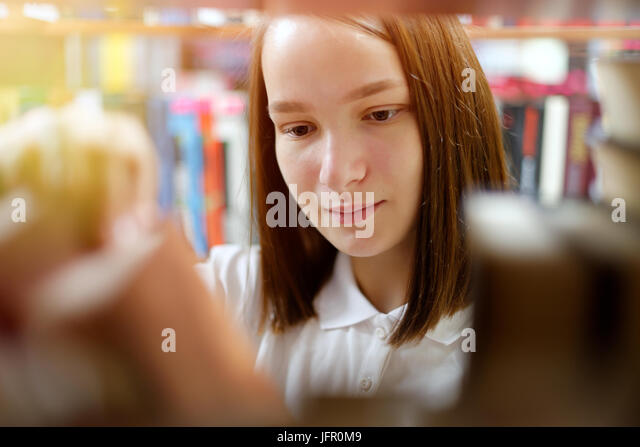 People: young girl, student, chooses a book in a library or bookstore, smiling, sunlight effect. - Stock Image