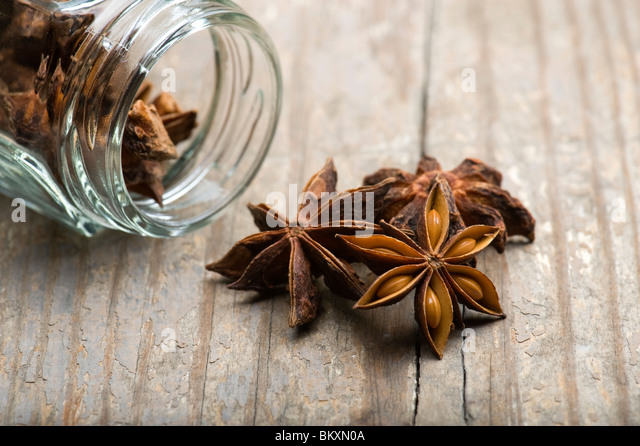Star Anise (Illicium verum) Spilling Out Of  Jar On A Wooden Kitchen Table - Stock Image