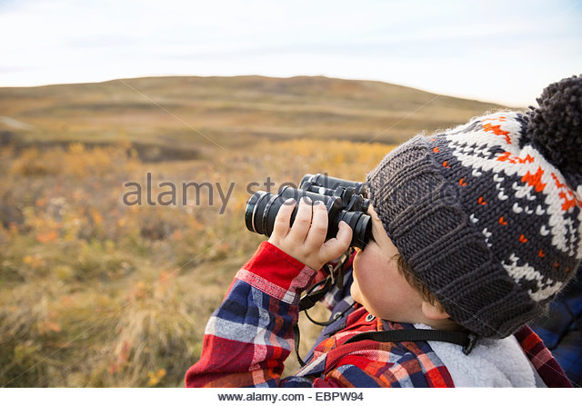 Boy with binoculars in rural field - Stock Image