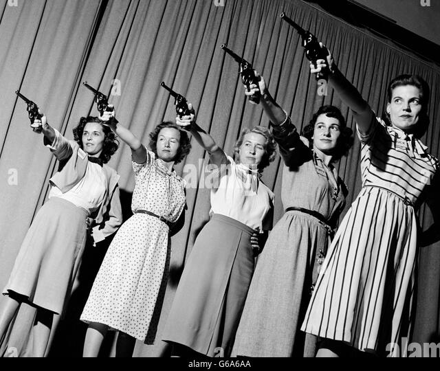1940s GROUP FIVE WOMEN IN A LINE AIMING PISTOLS - Stock Image