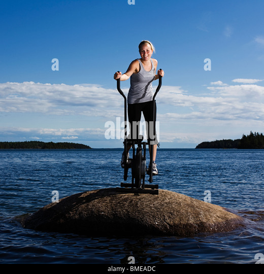 Young woman on a working out on a rock in a lake, Sweden. - Stock Image