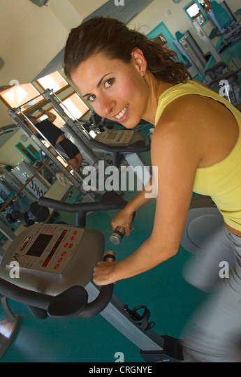 young woman on stationary bicycle in a health club - Stock Image