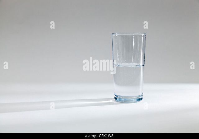 Glass half full half empty with water - Stock Image