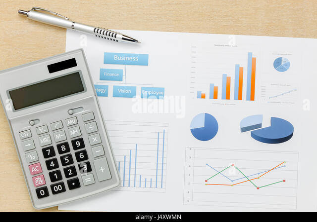 Top view business summary of the year and pen, chart calculator on wood  office desk background. - Stock Image