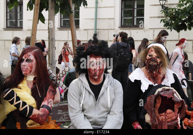 2 women and a man sitting on a bench, dressed up for the Zombie Walk in Prague, Europe in May 2014. - Stock Image