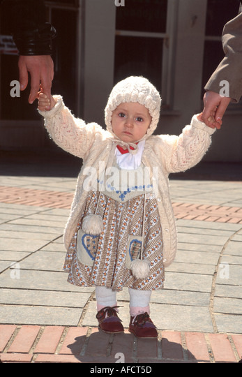 Turkey Istanbul Tunel Quarter Muslim toddler outside Galata Tower holds parents hands - Stock Image
