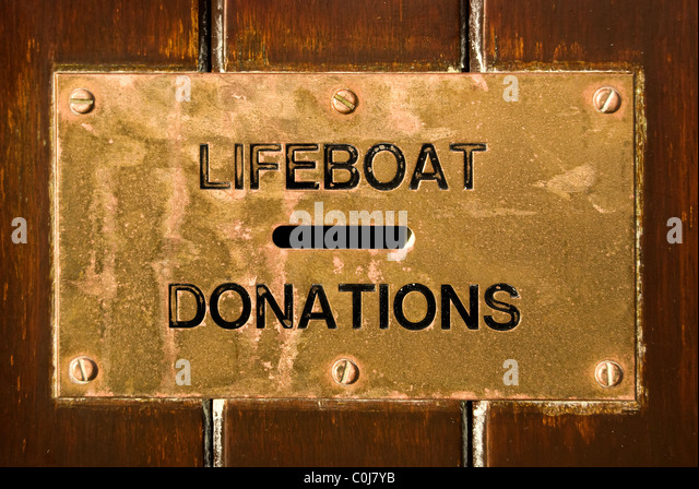 Brass Lifeboat Donations box at Porthcawl Lifeboat station, south Wales, UK - Stock Image