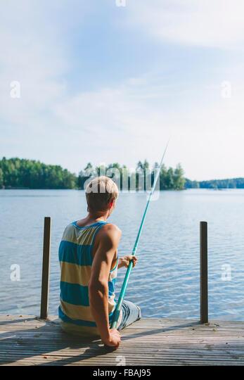Finland, Pirkanmaa, Salmentaka, Lake Palkanevesi, Young man fishing off lake pier - Stock Image