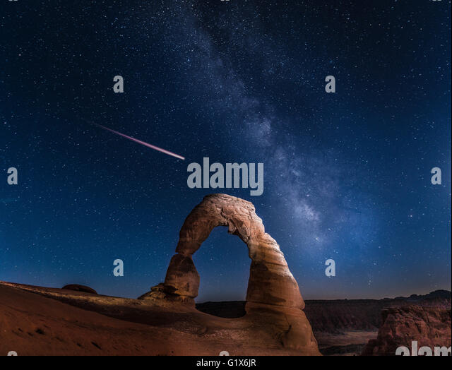 Natural Arch Delicate Arch with Milky Way and shooting star at night, Arches National Park, Moab, Utah, USA - Stock Image
