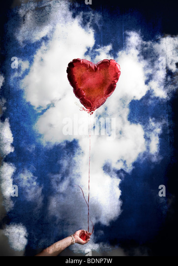 A girl holds a red balloon shaped liked a heart against the blue sky. - Stock-Bilder