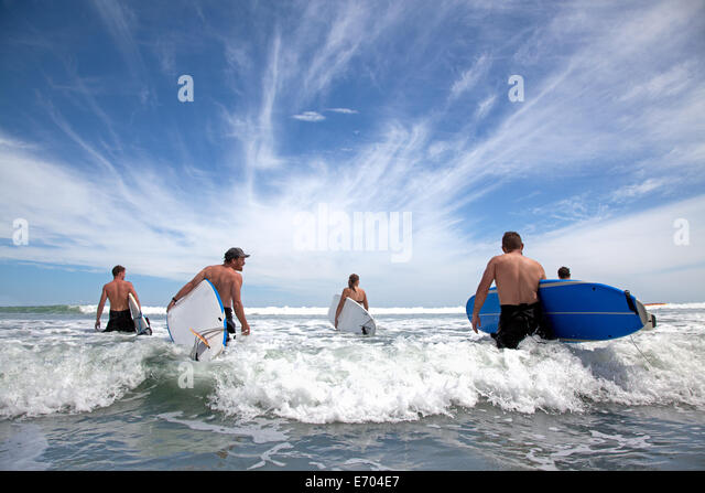 Group of male and female surfer friends wading into sea with surf boards - Stock-Bilder