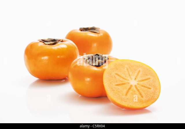 Kaki fruits, and sliced Kaki fruit - Stock Image