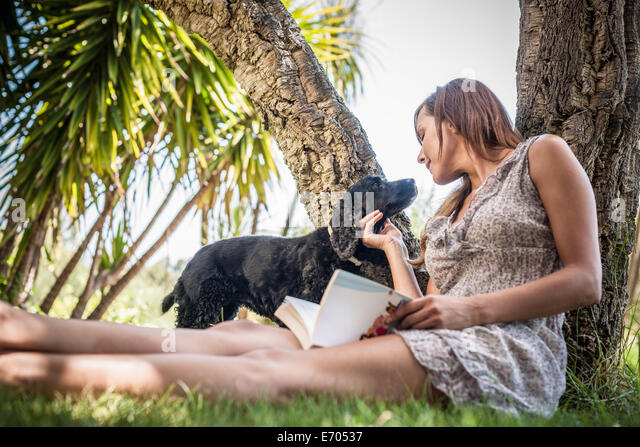Mid adult woman petting dog in holiday home garden, Capoterra, Sardinia, Italy - Stock-Bilder