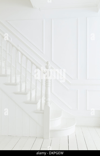 Banister and staircase in white foyer - Stock Image