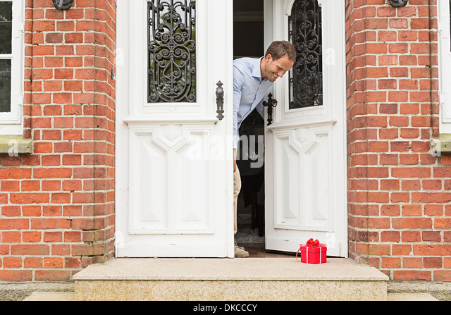 Mid adult man with gift on front doorstep - Stock Image