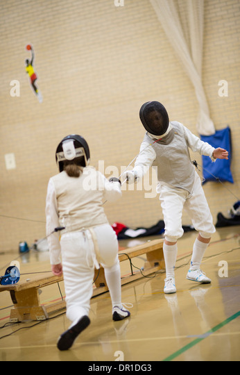 Two women Aberystwyth university students wearing safety masks competing at fencing (foil) , UK - Stock Image