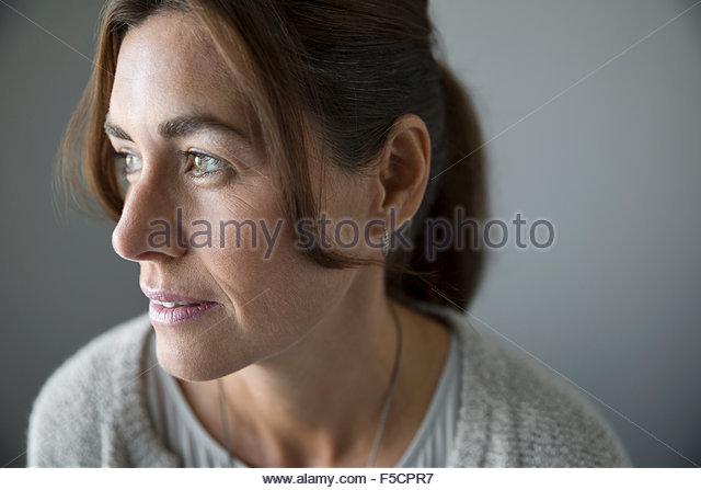 Close up pensive brunette woman looking away - Stock-Bilder