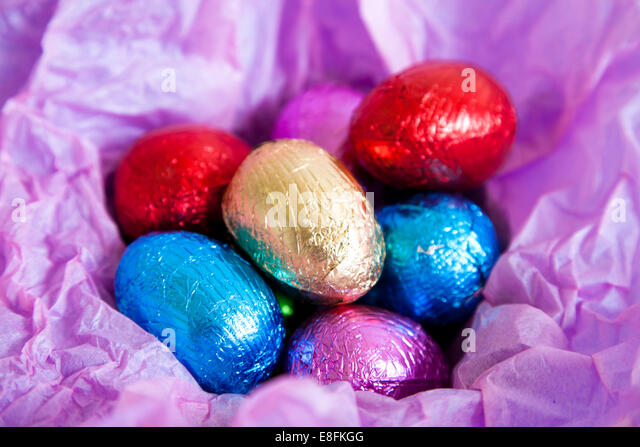 Multi colored foil covered Easter eggs - Stock Image