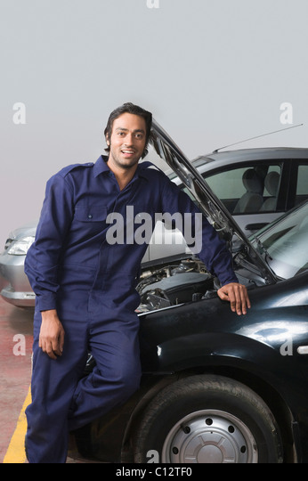 Auto mechanic leaning on a car in a garage - Stock Image