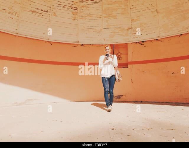 Full Length Of A Young Woman With Camera Phone Against Wall - Stock Image