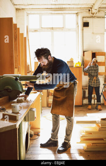 Mid adult craftsman using machinery in organ workshop - Stock Image