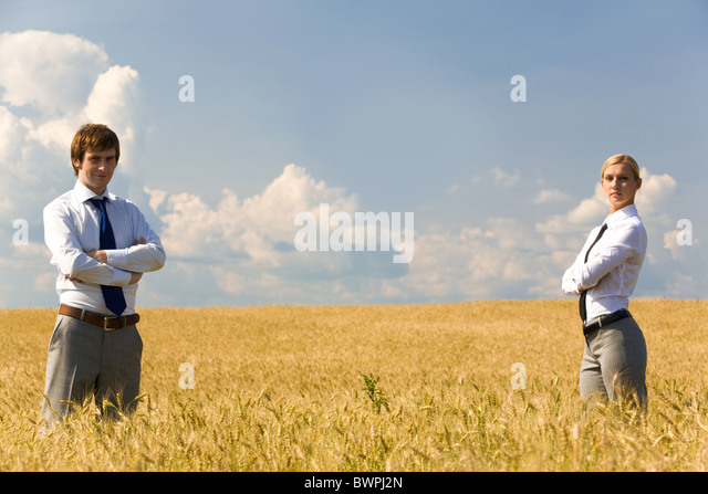 Contemporary business partners standing in wheat field - Stock-Bilder