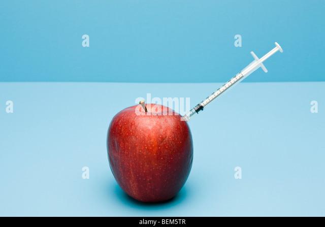 Food concept, syringe sticking out of apple - Stock-Bilder