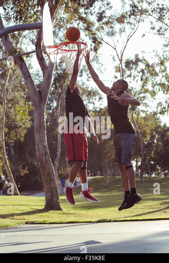 Two young men shooting basketball hoops in the park at sunset - Stock Image