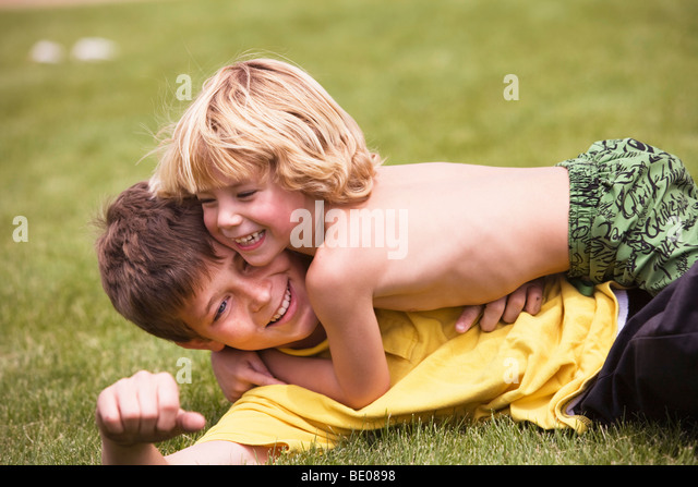 young boy wrestling with brother - Stock Image