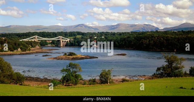 Menai suspension bridge over the Menai Straits, Anglesey, North Wales, UK.  The Carneddau mountains, Snowdonia, - Stock Image