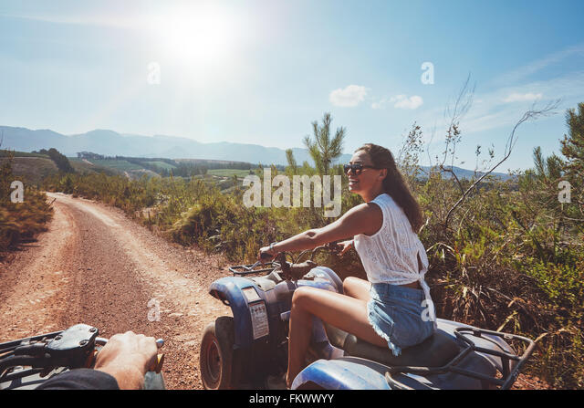 Young woman on quad bike on a trail. Young woman driving all terrain vehicle in nature on a sunny day. - Stock Image