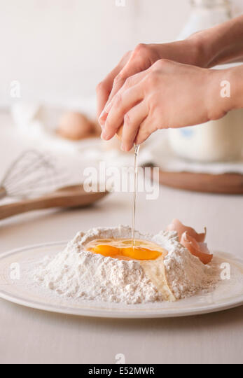Raw egg being cracked open into flour. Baking tools and ingredients in the background. - Stock Image
