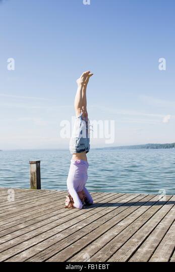 Mature woman on pier by ocean balancing on head - Stock-Bilder