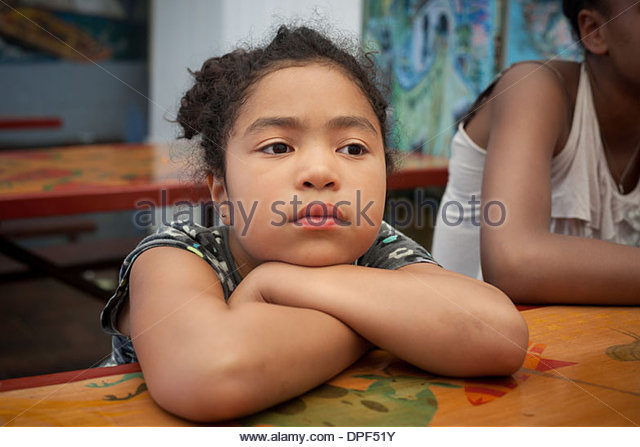 Sullen young girl sitting at outdoor table with arms folded - Stock Image