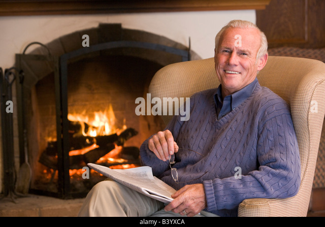 Man sitting in living room by fireplace with newspaper smiling - Stock Image