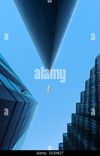 Aircraft flying over skyscrapers London UK - Stock Image