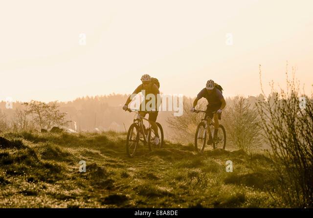 Young men mountainbiking at sunrise, Bavaria, Germany - Stock Image