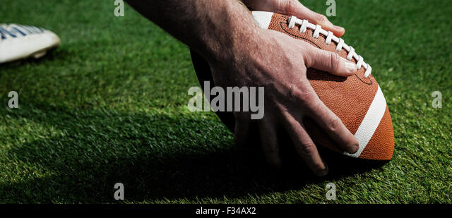 Close up view of american football player preparing for a drop kick - Stock Image