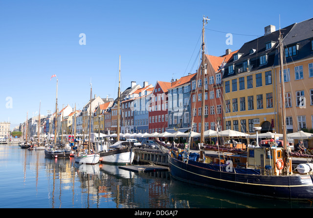 Nyhavn, Copenhagen is a popular destination for socialising with its colorful dockside bars and restaurants - Stock Image