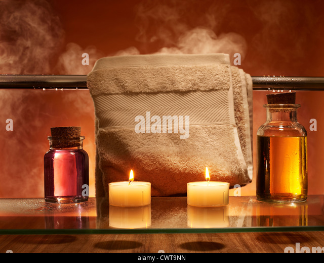 Candles and bath oils steamy bathroom and towel rail - Stock Image