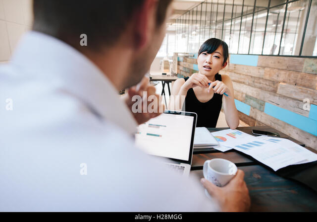 Shot of two businesspeople discussing work while sitting in office. Woman in meeting with office manager. - Stock Image