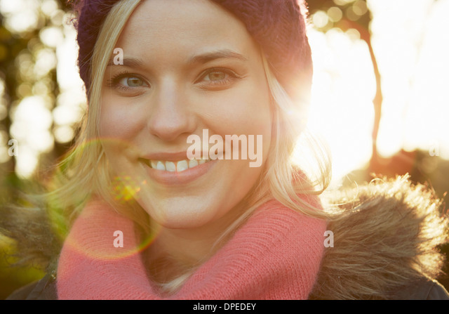 Portrait of young woman in park, wearing knit hat and scarf - Stock Image