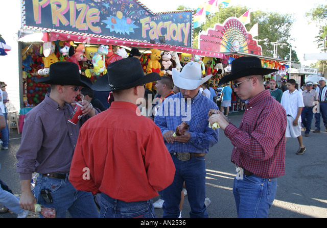 Albuquerque New Mexico State Fair carnival midway cowboys eat turkey legs W - Stock Image