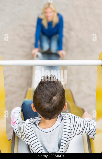 High angle view of boy sliding towards mother at playground - Stock Image