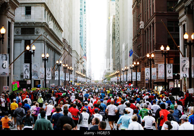 Large group of marathon joggers running through city street with tall buildings. - Stock Image