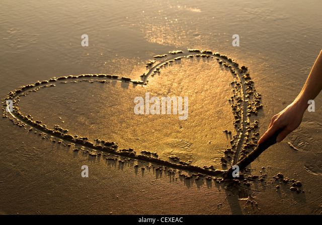 Heart shape etched into the sand on a beach at sunset with a female hand holding a stick; Newport, Oregon, USA - Stock Image