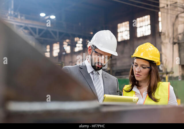 Manager and female steel worker meeting in factory - Stock Image