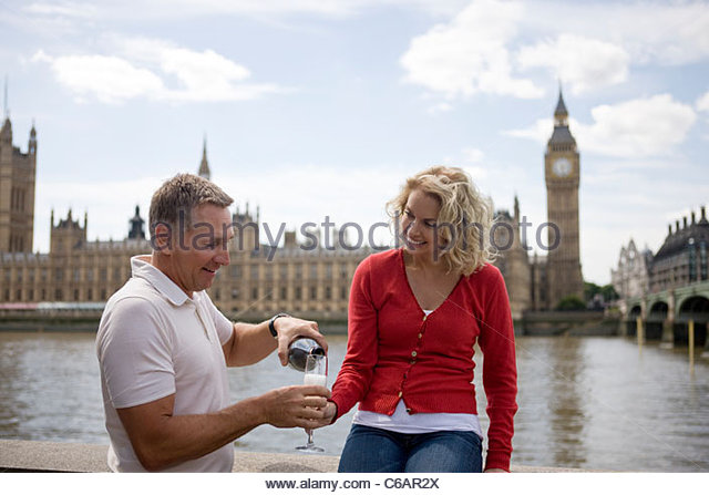 A middle-aged couple in front of the Houses of Parliament, man pouring champagne - Stock Image