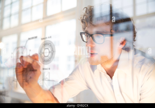 Portrait of young architect marking construction plan in office - Stock-Bilder