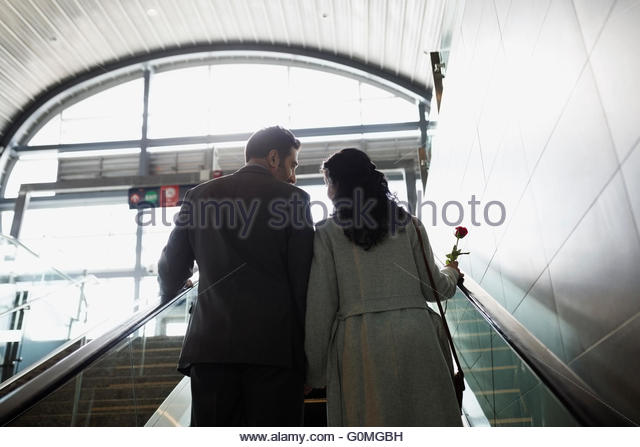 Couple ascending escalator at train station - Stock Image